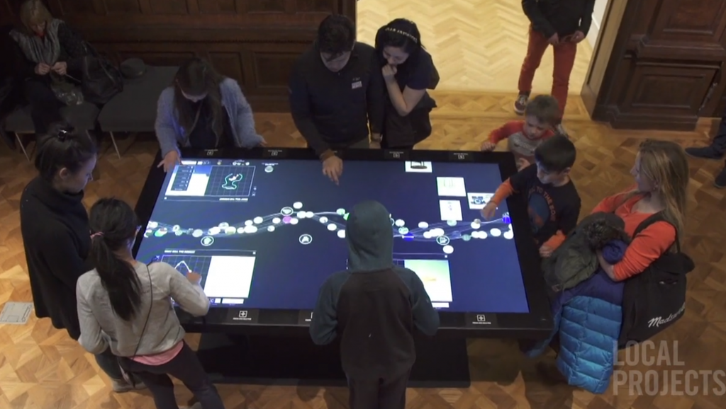 Still frame from video produced by Local         Projects showing social use of interactive tables.